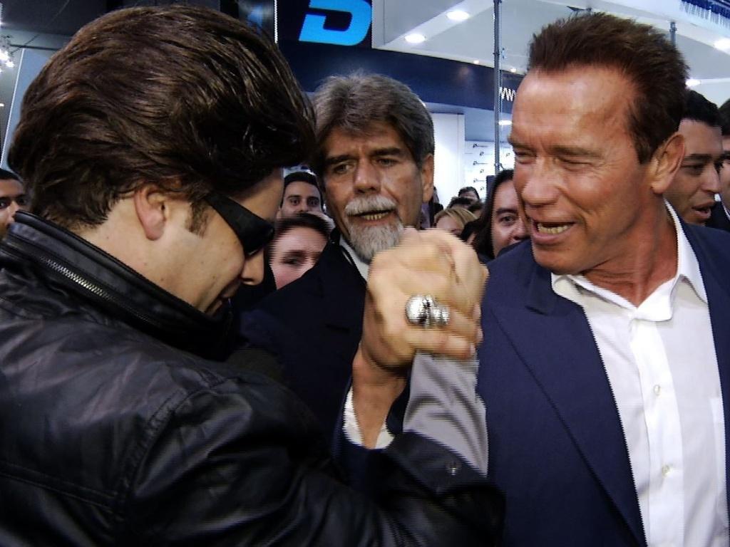26.abr.2013 - Arnold Schwarzenegger enfrenta repórter Vesgo em disputa de braço de ferro durante evento no Rio