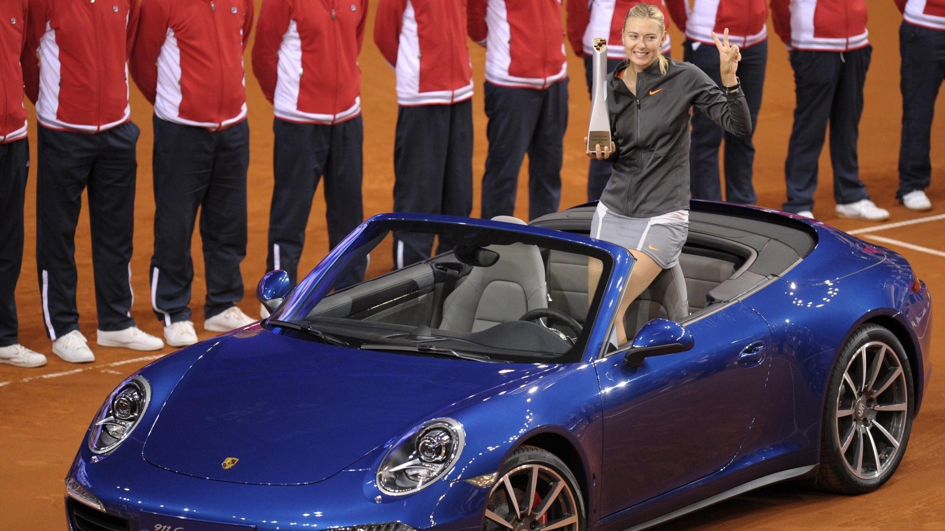 28.abr.2013 - Do Porshe 911 4S que ganhou, Maria Sharapova exibe troféu do Torneio de Stuttgart, na Alemanha