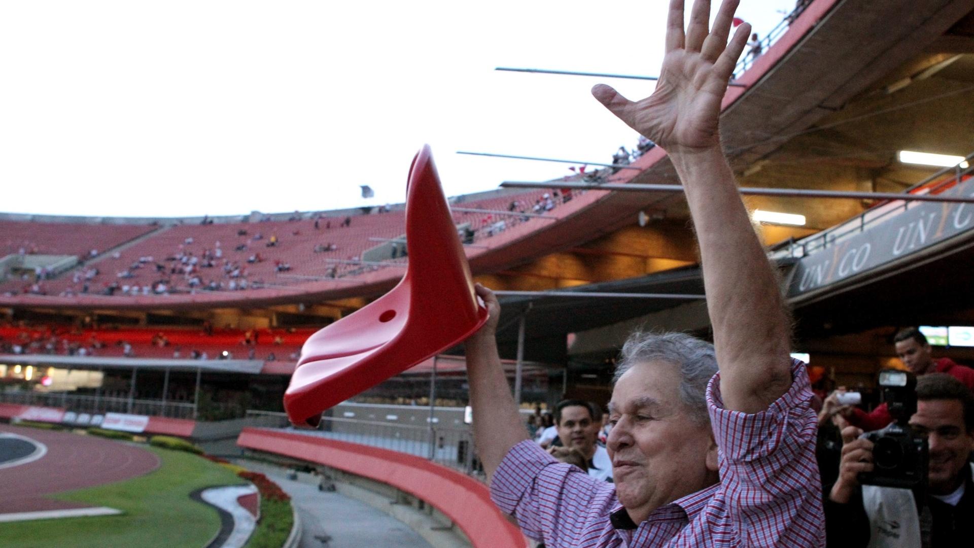 O presidente do São Paulo levanta cadeira vermelha como símbolo da campanha