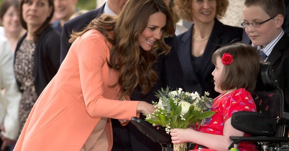 29.abr.2013 - Kate Middleton recebe flores de uma menina chamada Sally Evans ao visitar a instituição Naomi House, que cuida de crianças e adultos em estado terminal