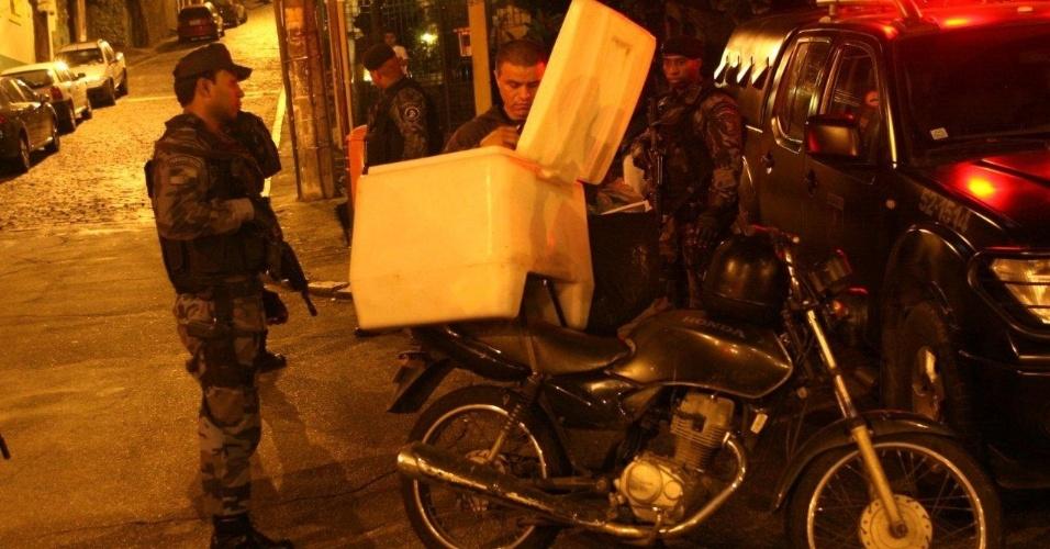 29.abr.2013 - Policiais revistam motoboy durante ocupação da comunidade do Cerro Corá, no Cosme Velho, zona sul do Rio de Janeiro. A ação ocorre às vésperas da visita do papa à cidade durante a Jornada Mundial da Juventude, que será realizada entre 23 e 28 de julho