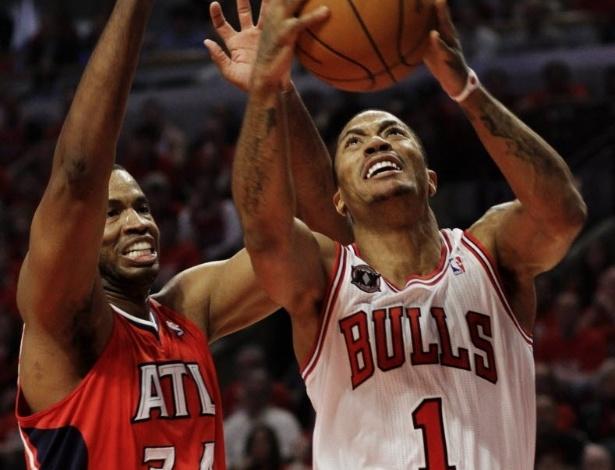 10.mai.2011 - Derrick Rose, do Chicago Bulls, tenta infiltração contra a marcação de Jason Collins, do Atlanta Hawks, em partida válida pelos playoffs