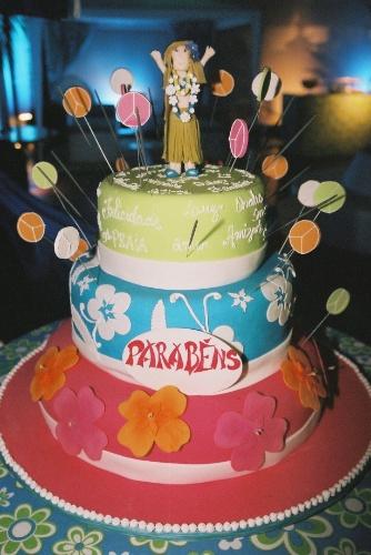 O bolo de pasta americana com três andares foi confeitado com as cores e os elementos temáticos da festa decorada por Cristiane Pileggi. No topo, uma bonequinha da aniversariante em trajes havaianos