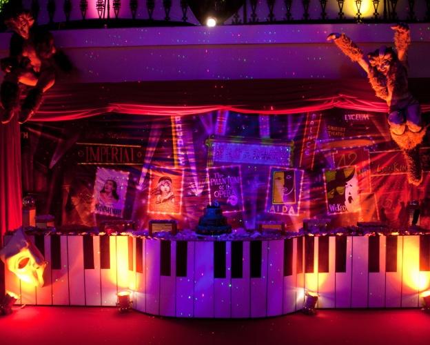 Para compor a mesa de doces e bolo dessa festa de aniversário com tema Broadway, a decoradora Roberta Niemeyer criou um painel com cartazes de musicais famosos