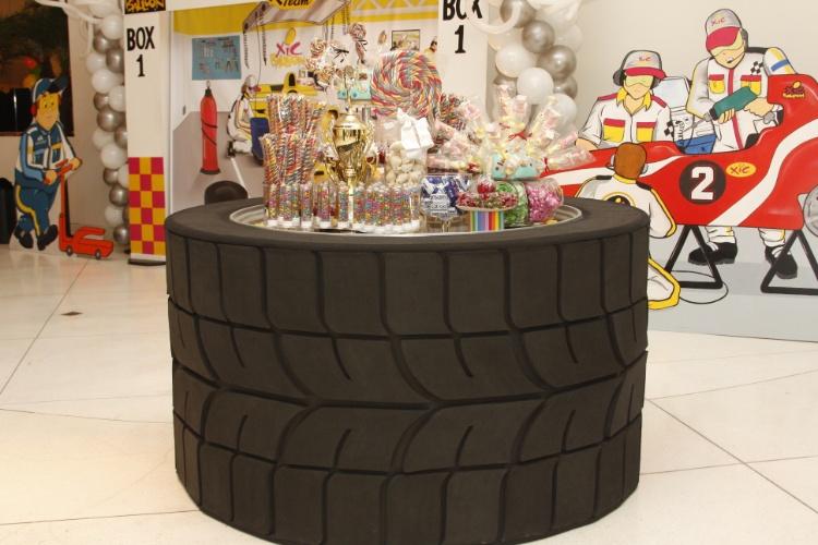 Para os garotos, um tema atual e divertido é Fórmula 1. Nesse aniversário de dois irmãos, um de 14 anos e outro de 12, a mesa de doces foi decorada para parecer um grande pneu de carro