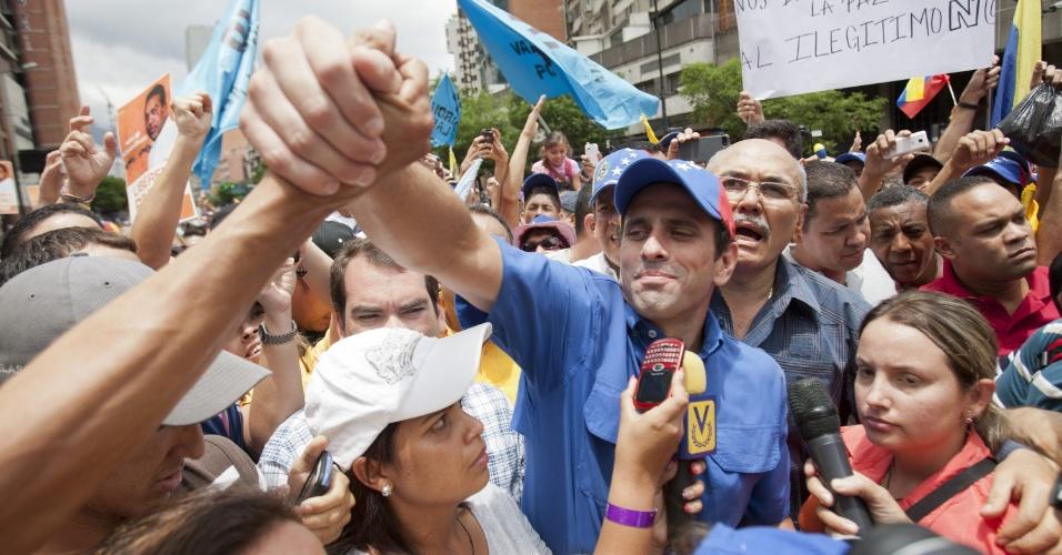1º.mai.2013 - O líder da oposição venezuelana Henrique Capriles cumprimenta apoiadores duranta ato pelo Dia do Trabalho em Caracas (Venezuela), nesta quarta-feira (1º). Capriles anunciou que a oposição impugnará nesta quinta-feira (2), no Tribunal Supremo de Justiça, os resultados das eleições presidenciais de 14 de abril, nas quais o presidente Nicolás Maduro venceu o líder opositor por uma vantagem apertada nas urnas