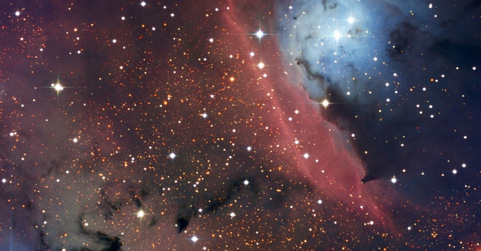 2.mai.2013 - Telescópio dinamarquês do Observatório La Silla, no Chile, fez novas imagens da nebulosa NGC 6559, que fica a 5.000 anos-luz de distância da Terra, na constelação de Sagitário. Essa nuvem de gás e poeira é um pequeno berçário de estrelas, com poucos anos-luz de dimensão. Segundo o Observatório Europeu do Sul (ESO, na sigla em inglês), a radiação emitida pelas estrelas recém-nascidas é reenviada pelo hidrogênio gasoso da nuvem, criando essa região vermelha no centro da imagem. Já a mancha azulada, que está próxima da nebulosa de emissão vermelha, indica a radiação emitida pelas novas estrelas que é dispersada em várias direções pelas partículas microscópicas e sólidas que existem na NGC 6559 - poeira compostas por elementos pesados, como carbono, ferro ou silício