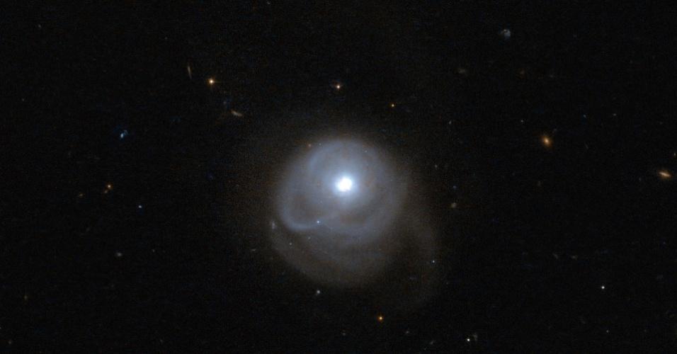 6.mai.2013 - O telescópio espacial Hubble detectou uma galáxia que chama a atenção por seu formato diferente. Catalogada como 2MASX J05210136-2521450, ela emite grande quantidade de luz no comprimento de onda infravermelho devido à intensa formação de estrelas, que foi impulsionada pela fusão de duas galáxias no local. Segundo a Agência Espacial Europeia (ESA, na sigla em inglês), a força gravitacional da fusão fez seus braços internos serem direcionados para um lado e o rabo para a direção oposta, criando uma espécie de casulo em volta do núcleo brilhante da 2MASX J05210136-2521450