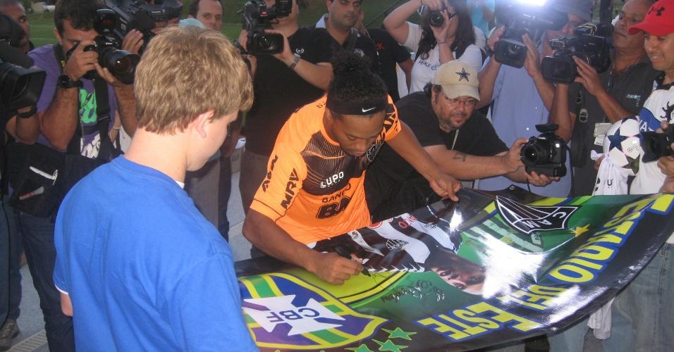 07/05/2013 - Ronaldinho Gaúcho dá autógrafo em um pôster para o jovem torcedor norte-americano