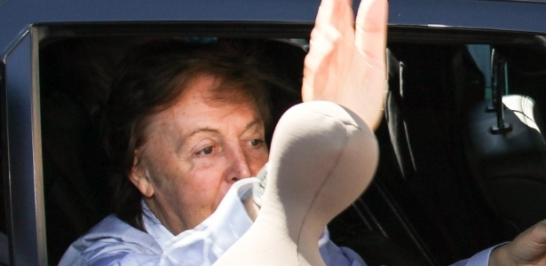 7.mai.2013 - Sorridente, Paul McCartney abre vidro de carro e cumprimenta fãs ao deixar hotel em Goiânia