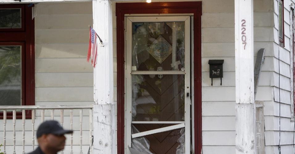 7.mai.2013 - Agente da polícia passa próximo à porta que foi derrubada por um vizinho após uma das três mulheres, que ali estavam trancadas há dez anos, conseguir pedir ajuda. Amanda Berry, Gina DeJesus e Michele Knight, foram encontradas na avenida Seymour, em Cleveland, Ohio (EUA). Os três suspeitos de ligação com o caso foram presos e serão interrogados