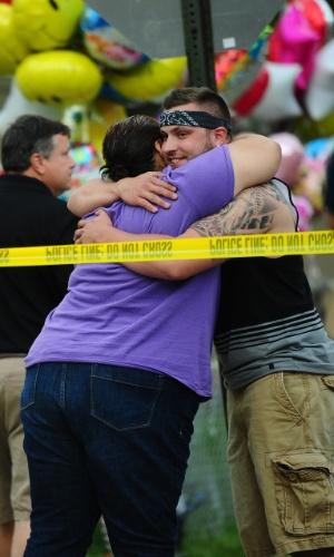 7.mai.2013 - Amigos e parentes se abraçam em frente à casa da família de Gina DeJesus. Ela, Amanda Berry e Michelle Knight, que desapareceram há cerca de dez anos, foram encontradas no sul da cidade de Cleveland, Ohio (EUA). Segundo a polícia, três irmãos hispânicos foram detidos pela relação com o sequestro