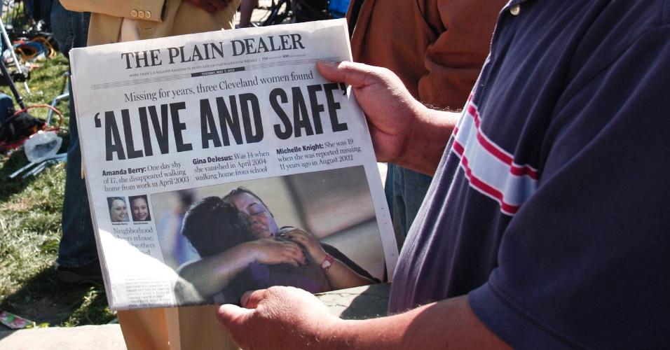 """7.mai.2013 - Homem mostra capa do jornal local """"The Plain Dealer"""" que destaca o reaparecimento das três mulheres mantidas em cativeiro durante cerca de 10 anos, próximo à casa onde elas viviam. Amanda Berry, Gina DeJesus e Michele Knight, foram encontradas após uma delas conseguir, por meio de um buraco na porta principal, pedir ajuda a um vizinho. Os três suspeitos de ligação com o caso foram presos e serão interrogados"""