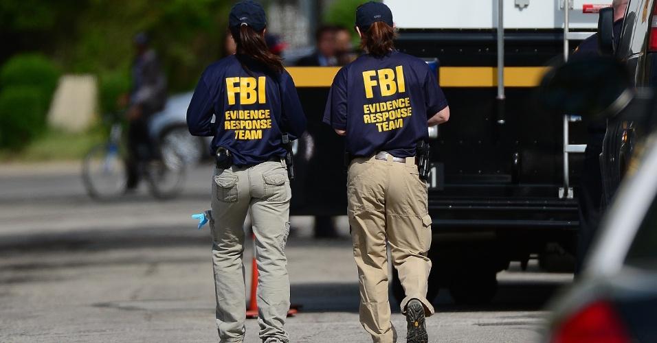 8.mai.2013 - Agentes do FBI (polícia federal norte-americana) fazem buscas em casa onde três mulheres que estavam desaparecidas foram encontradas com vida após quase dez anos em Cleveland, em Ohio (EUA). A polícia busca pistas que expliquem como elas foram mantidas em cativeiro por tanto tempo sem que ninguém percebesse. As jovens foram ouvidas nesta terça-feira. Os três homens detidos suspeitos pelos sequestros serão interrogados nesta quarta-feira (8)