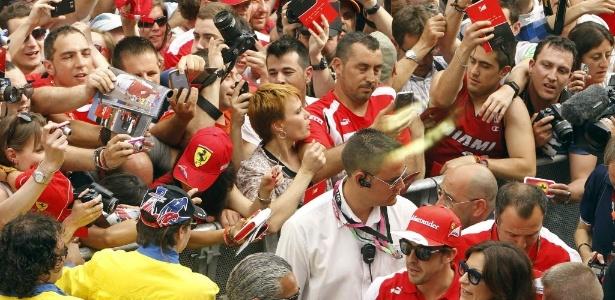 Fãs cercam Fernando Alonso e tentam pegar um autógrafo do piloto da Ferrari