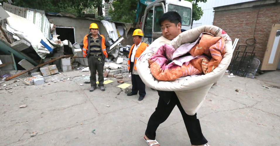 9.mai.2013 - Morador olha para trás enquanto leva pertences durante reintegração de posse em Pequim, na China. As casas foram construídas sem permissão em uma área de 4 km e serão derrubadas