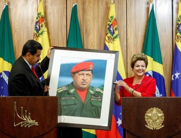 9.mai.2013 - Presidente Dilma Rousseff recebe quadro do ex-presidente venezuelano Hugo Chávez das mãos do atual ocupante do cargo, Nicolás Maduro. Ele veio ao Brasil agradecer pelo apoio de Dilma durante as eleições na Venezuela e foi alvo de protestos que questionaram a legitimidade do pleito