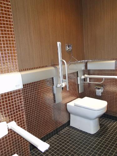Para prevenir acidentes, seja o usuário idoso ou com mobilidade reduzida, a área do vaso sanitário do banheiro projetado por Robson Gonzales recebeu barras de apoio. O acionamento da válvula é em alavanca, que pode ser realizado com facilidade, seguindo os conceitos do Desenho Universal