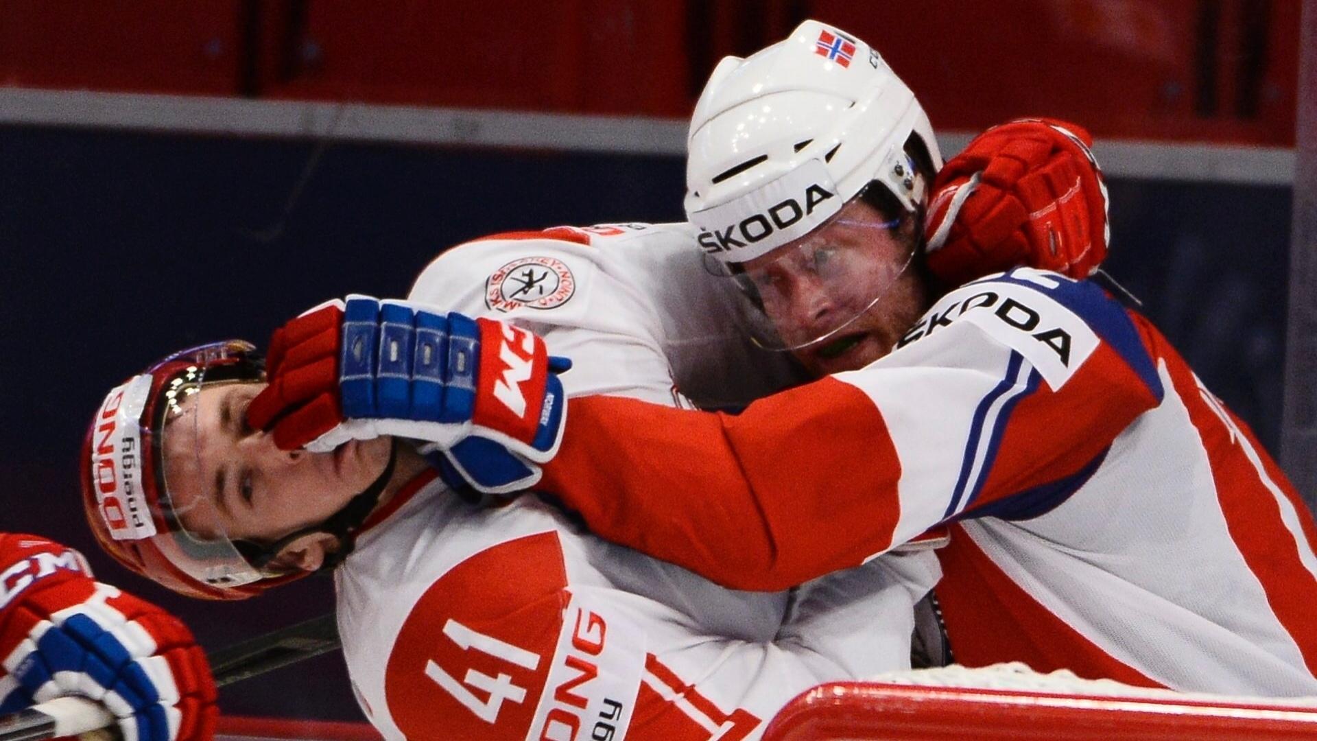05.mai.2013 - Martin Roymark (dir), da Noruega, dispara um direto no rosto de Jesper Jensen, da Dinamarca, durante partida pelo Mundial de hóquei no gelo