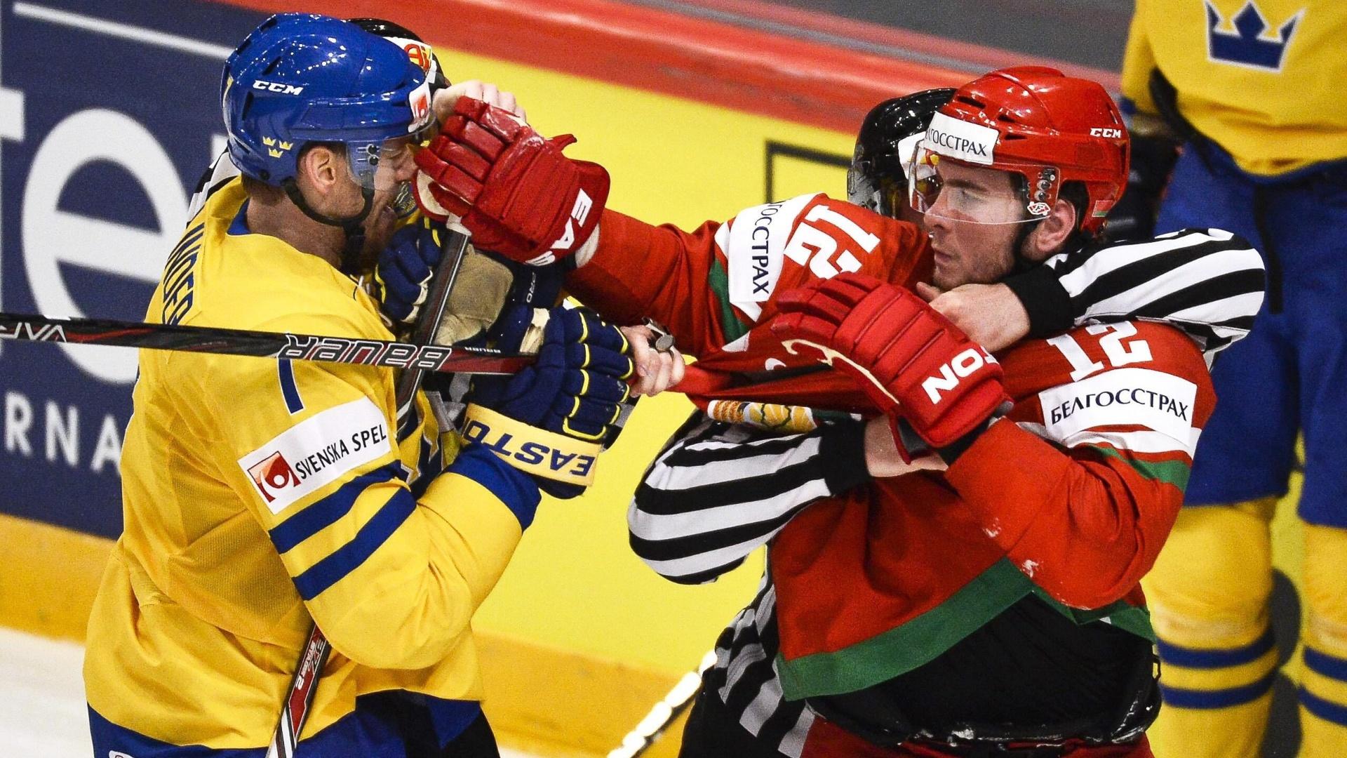 06.mai.2013 - Andrei Filichkin (dir), de Belarus, tenta socar Henrik Tallinder, da Suécia, durante partida pelo Mundial de hóquei no gelo