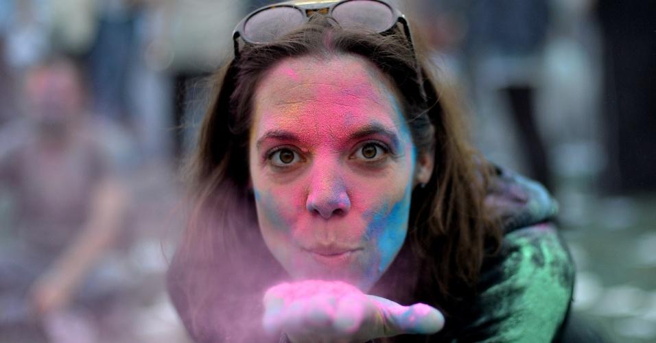 11.mai.2013 - Mulher sopra pó colorido durante o festival Holi, em Berlim, na Alemanha. Originalmente festejado por hindus no norte da Índia, a festa celebra a chegada da primavera