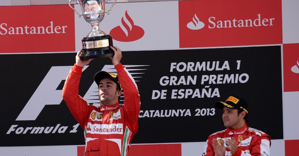 12.mai.2013 - Aplaudido por Felipe Massa, terceiro colocado, Fernando Alonso ergue o troféu conquistado após vencer o GP da Espanha
