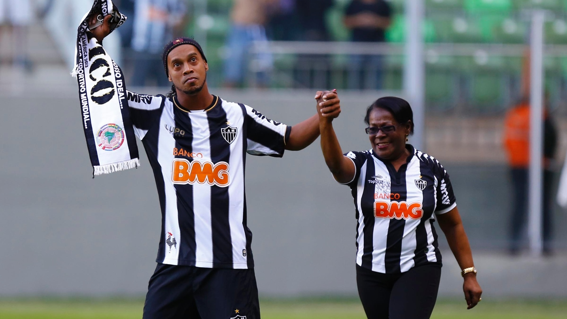 12.mai.2013 - Ronaldinho Gacho leva a me at o gramado para ser homenageada pelos torcedores atleticanos antes do jogo contra o Cruzeiro