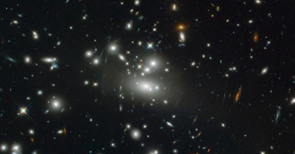 14.mai.2013 - As galáxias do centro da Abell S1077 aparecem como manchas brilhantes no registro feito pelo telescópio Hubble, devido à força do seu campo gravitacional. Segundo a Agência Espacial Europeia (ESA,na sigla em inglês), o aglomerado de galáxias age como uma lupa e estica a luz que viaja desde o centro rumo à Terra