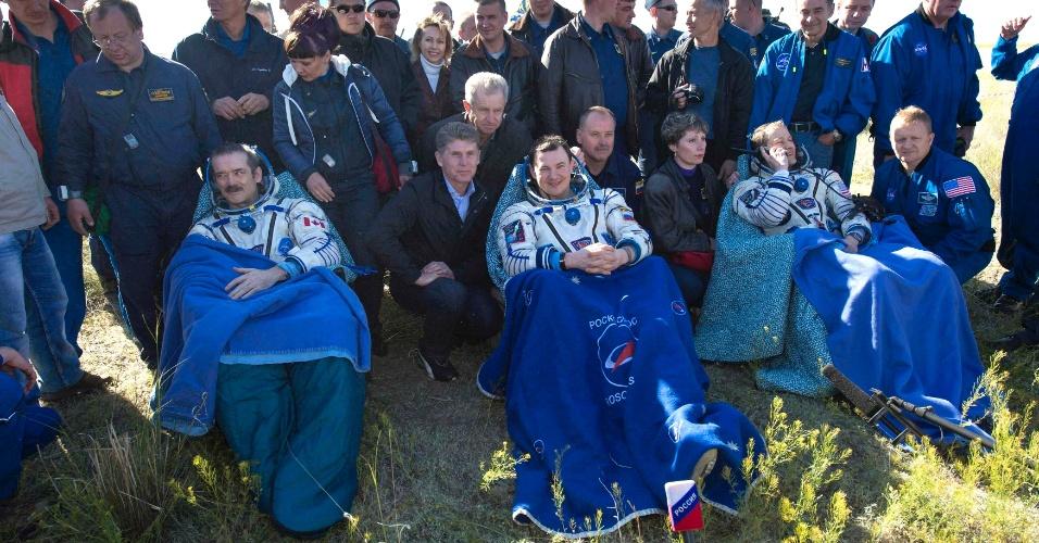 14.mai.2013 - O astronauta canadense Chris Hadfield (esq.), o norte-americano Tom Marshburn (dir.), e o cosmonauta russo Roman Romanenko (centro) descansam após deixarem a cápsula espacial russa Soyuz. O primeiro astronauta canadense a comandar uma missão na Estação Espacial Internacional trouxe a tripulação de volta à Terra, aterrissando a cerca de 150 km a sudeste da cidade de Zhezkazgan, no centro Cazaquistão, depois de passarem cinco meses no espaço