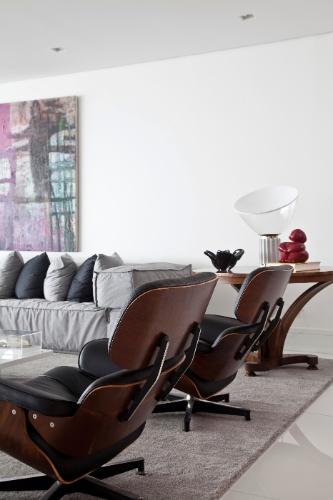 No apartamento com projeto de interiores da SQ+Arquitetos Associados, o sofá da área de estar tem composição modular e acompanha duas cadeiras Charles Eames (Toque da Casa). O quadro é da Galeria Roberto Alban e a luminária Taccia, sobre a mesa de canto, é da Omni Light