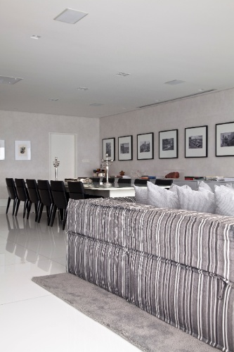Os ambientes de jantar e home theater se integram no apê Corredor da Vitória 2, assinado pelo arquiteto Sidney Quintela. O sofá modular em Jacquard listrado, de tom acinzentado neutro, dialoga com o papel de parede com textura, em tonalidade grafite. A ideia é destacar as cores dos objetos de decoração (livros, pratarias) e das esculturas de Ricardo Teixeira, em caixas acrílicas, sobre o aparador