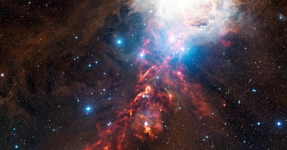 15.mai.2013 - Uma fita flamejante corta uma região da constelação de Órion, que é conhecida por apresentar uma mistura de nebulosas brilhantes, estrelas quentes jovens e nuvens de poeira fria a 1350 anos-luz da Terra, mostra registro do telescópio Apex, no Chile. De acordo com o Observatório Europeu do Sul (ESO, na sigla em inglês), o brilho laranja indica a radiação emitida pelos grãos frios em comprimentos de onda longos demais para serem vistos pelo olho humano. Já o intenso clarão (acima, à direita) mostra a Nebulosa de Órion, também chamada de Messier 42, a maternidade de estrelas de grande massa mais próxima do nosso planeta