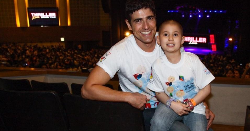 15.mai.2013 - O ator Reynaldo Gianecchini posa com beneficiada com o tratamento oferecido pelo GRAACC (Grupo de Apoio ao Adolescente e à Criança com Câncer) no espetáculo
