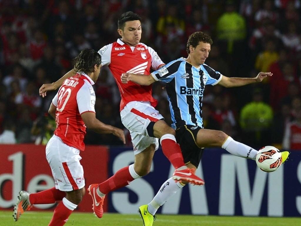 16.mai.2013 - Elano sofre com a marcação dos adversários na partida entre Grêmio e Independiente Santa Fé pela Libertadores