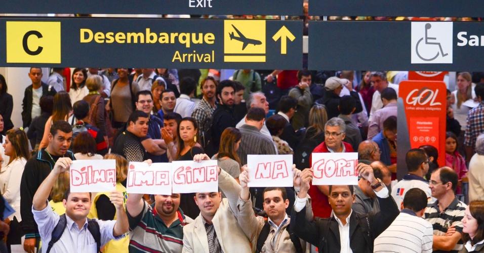 "17.mai.2013 - Grupo de passageiros participa de protesto no Aeroporto Santos Dumont, no centro do Rio de Janeiro, após o local ser fechado para pousos e decolagens por causa da chuva. Nos cartazes, se lê: ""Dilma, imagina na Copa"""