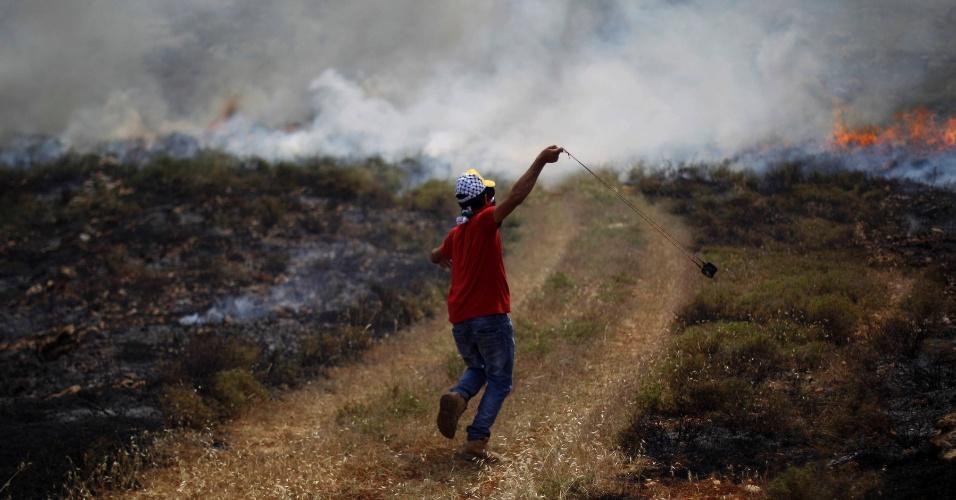 17.mai.2013 - Manifestante palestino usa estilingue para atirar pedras em soldados israelenses durante confrontos na aldeia Deir Jarir, na Cisjordânia