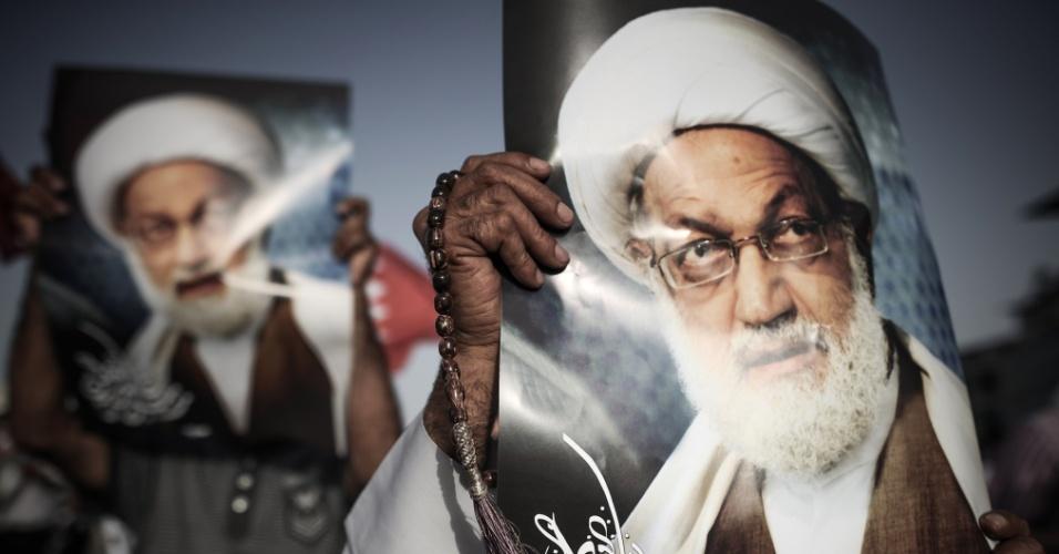 17.mai.2013 - Manifestantes exibem foto do líder clérigo xiita Sheikh Issa Qassem durante protesto contra o governo de bareinita na aldeia de Abu Saiba, oeste de Manama (Bahrein). O principal partido de oposição acusou as tropas do governo de invadir a casa de Qassem