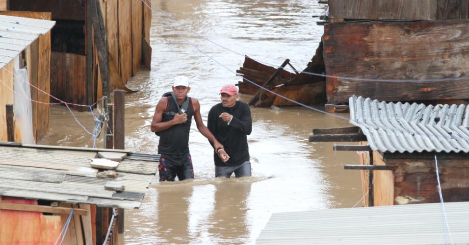 17.mai.2013 - Moradores da Comunidade Sapo Nú, que fica às margens da BR-232, em Recife(PE), caminham por rua completadamente ilhada após forte temporal. Duas crianças da região foram arrastadas pela força da água