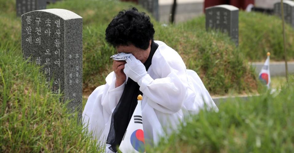 17.mai.2013 - Mulher chora na frente ao túmulo de uma das vítimas do massacre de Gwangju, ao sul de Seul, na Coreia do Sul. Em 1980, o governo militar liderado por Chun Doo-Hwan e Roh Tae-woo matou milhares de civis que eram contra o regime militar