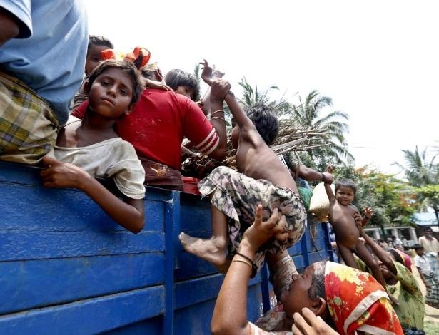 17.mai.2013 - Mulher empurra criança para que ela suba em carroceria de caminhão que se dirigia a acampamento em Sittwe, no Mianmar, em que pessoas estão sendo alocadas em medida de segurança devido à aproximação de ciclone