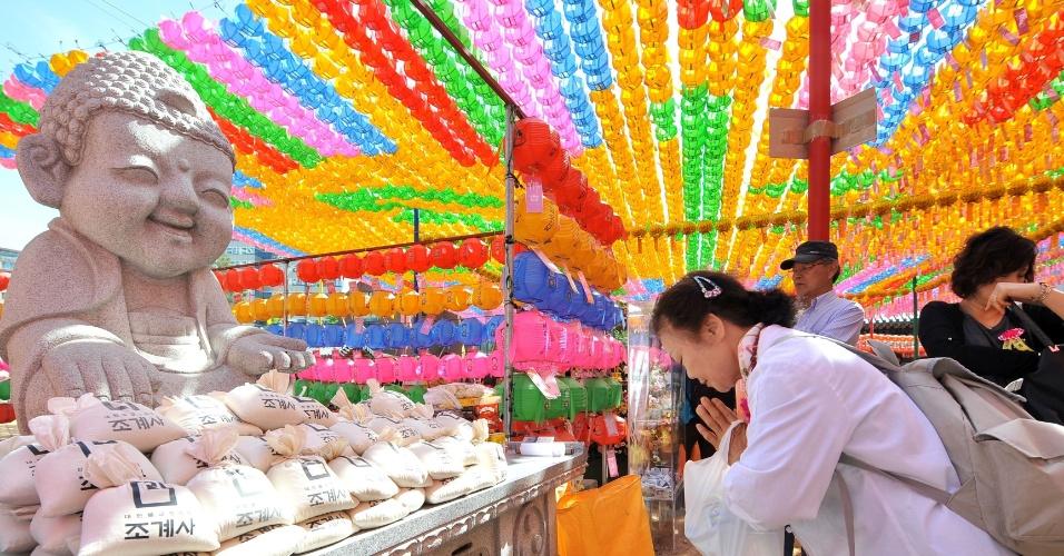 17.mai.2013 - Mulher ora sob fileiras de lanternas orientais com formato de lótus no templo Jogye, em Seul (Coreia do Sul) durante cerimônia que celebra o aniversário de Buda