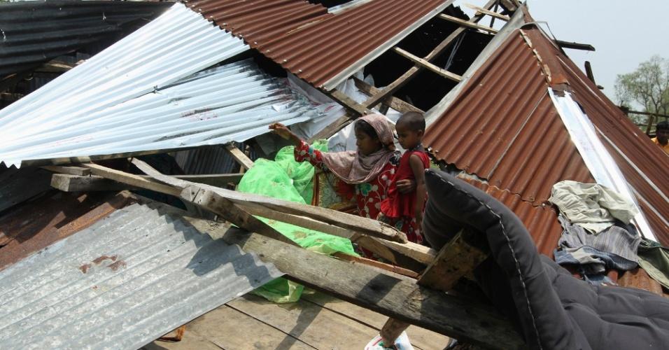 """17.mai.2013 - Mulher tenta recuperar pertences em casa destruída após a passagem do ciclone """"Mahasen"""", na cidade litorânea de Kuakata, Bangladesh. O número de mortos por causa do ciclone no país passou de 30"""