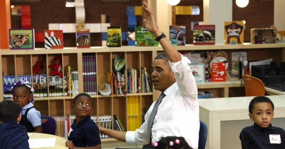 17.mai.2013 - O presidente dos EUA, Barack Obama, levanta a mão enquanto participa de aula em visita a escola infantil em Baltimore, em Maryland, nesta sexta-feira (17)