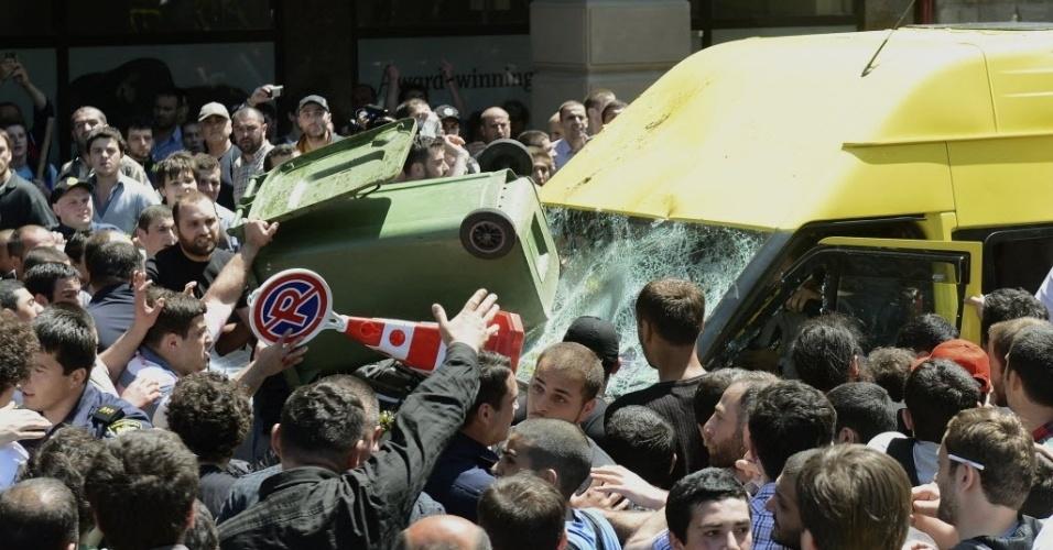 17.mai.2013 - Veículo que transportava ativistas das causas gays é cercado por multidão e tem para-brisa quebrado durante manifestações relacionadas ao Dia Internacional Contra a Homofobia em Tbilisi, capital da Geórgia, nesta sexta-feira (17)