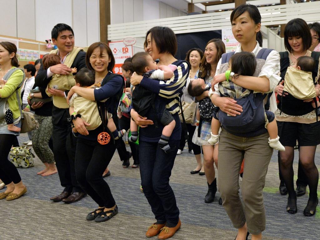 Dezenas de jovens pais dançam nesta sexta-feira (17) carregando seus bebês no evento Mama Fes em Tóquio (Japão)