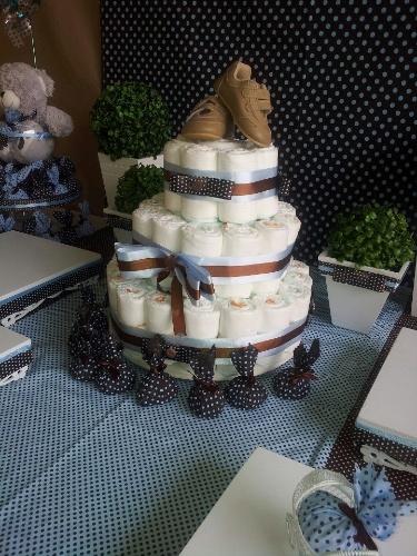 No topo do bolo de fraldas, chama atenção o sapatinho do bebê. Fazer o bolo é simples, basta enrolar diversas fraldas descartáveis, posicioná-las uma ao lado da outra, em formato de círculo. As fitas de cetim finalizam a produção.  www.facebook.com/robertalopes.anjos