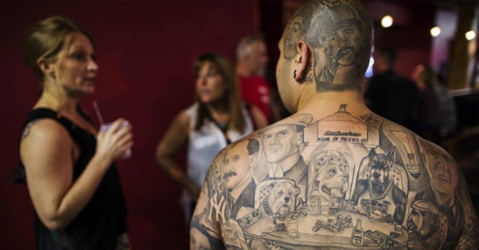 18.mai.2013 - Homem com rostos tatuados nas costas participa de encontro sobre o tema em Nova York
