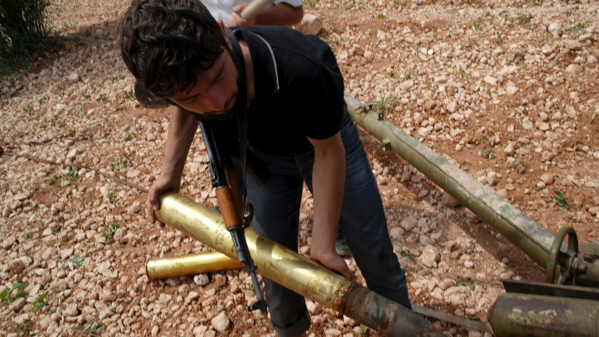 18.mai.2013 - Jovem carrega projtil de artilharia na zona rural de Aleppo, na Sria