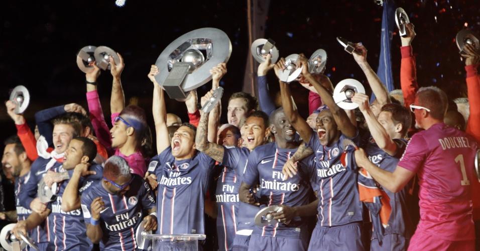 18.mai.2013 - Meia Lucas (esq) é abraçado por David Beckham enquanto Thiago Silva, capitão do Paris Saint-Germain, levanta a taça de Campeão Francês, entregue ao time após a vitória por 3 a 1 sobre o Brest, no Parque dos Príncipes
