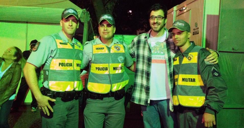 18.mai.2013 - Policiais tietam o humorista Rafinha Bastos antes de sua apresentação no Palco Sé da Virada Cultural 2013